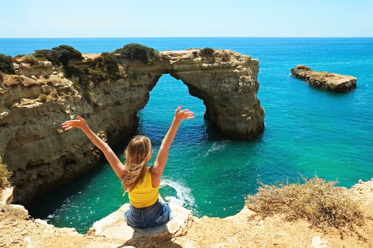 Young beautiful woman enjoying the panoramic top view of rocky beaches with cliffs somwhere, somwhere in Algarve, Portugal. Atlantic ocean shore background. Copy space for text.