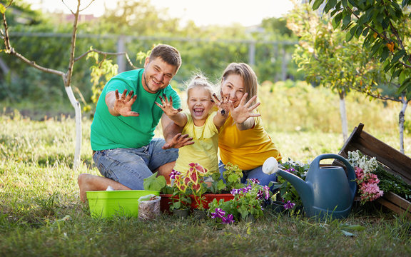 Happy family gardening together and taking care of nature. Plant sprouts and fertilize the ground. Hugging and having fun. Show dirty hands to the camera