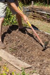 Au potager - jardinier traçant un sillon suivant un cordeau