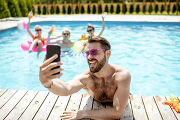 Handsome man takng selfie photo with phone, while resting in the swimming pool with friends outdoors during the summertime
