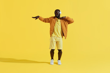 Man in headphones listening music, dancing on yellow background