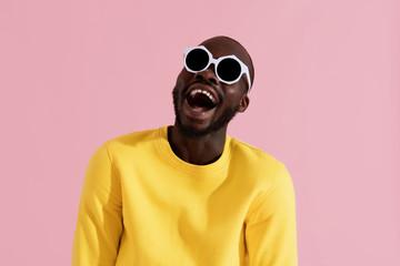 Fashion. Smiling black man in sunglasses colorful portrait Wall mural