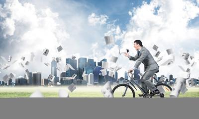 Businessman with megaphone in hand on bike