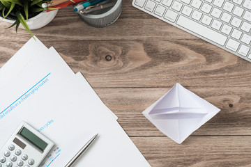 Wooden office desk with white origami boat.