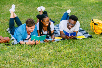 Handsome hipster man with african man and black woman students lying on a grass talking laughing reading books while doing homework at park in sunny meadow. Education and Friendship Concept.