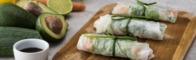 Fototapeta panoramic shot of spring rolls with soy sauce on cutting board obraz