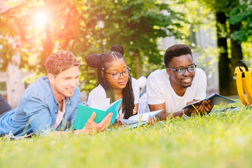 Front view of three happy multiethnic students lying, talking, joking together together on green lawn high school university campus. Education and Friendship Concept. Sun glare effect