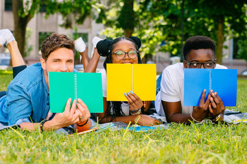 International male and female students covered faces books and whispering gossip or news on green lawn high school university campus. Education and Friendship Concept.