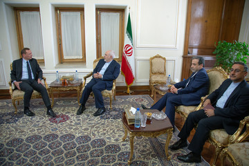 France's top diplomat Emmanuel Bonne shakes hands with Iran's Foreign Minister Mohammad Javad Zarif in Tehran