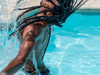 Black man with afro hair and dreadlocks comes out of the pool splashing water.