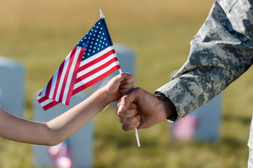 cropped view of military father and daughter holding american flag