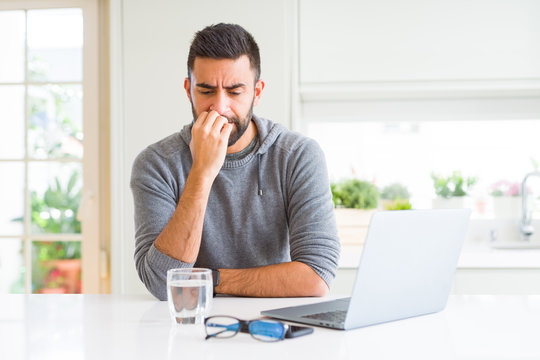Handsome hispanic man working using computer laptop looking stressed and nervous with hands on mouth biting nails. Anxiety problem.