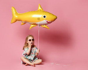 little girl, dressed in a summer dress, wears a balloon in the shape of a yellow shark-fish, celebrates a holiday, smiles broadly, stands against a pink background, is in a good mood.