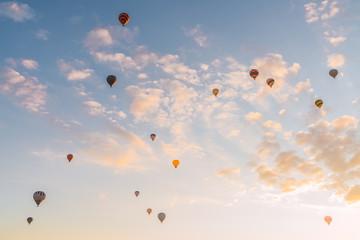 Many hot air balloons flying against sunny sundown sky during festival in Cappadocia