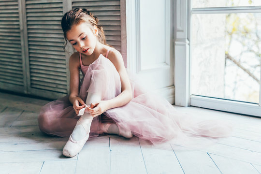 Young classical ballet dancer girl in dance class. Beautiful graceful ballerina in pink tutu skirt puts on pointe shoes near large window in white light hall