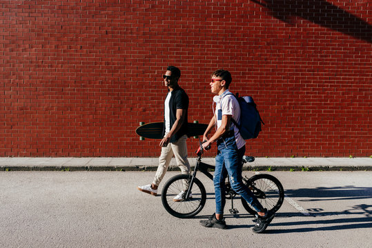 Side view of young black joyful successful male friends in sunglasses walking in city with bicycle and skateboard