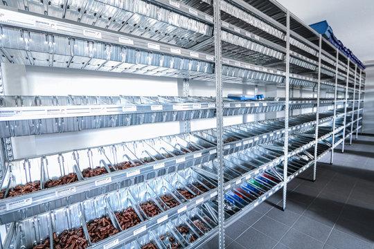Ein langes Industrie Edelstahl-Regal mit Boxen, die mit verschiedenen Kupferteilen gefüllt sind. Schönes Licht-Schatten Spiel.