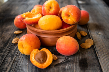 Fresh organic apricots in a clay bowl on old wooden table
