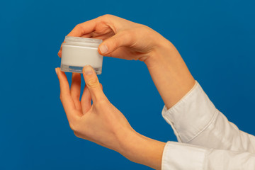 Woman's hands holding cosmetic cream container on blue