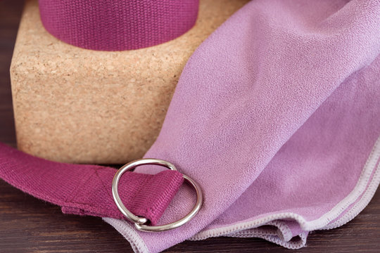 Close up of yoga props,cork blocks, violet yoga strap and lilac towel  for doing yoga on wooden floor. Yoga props background.