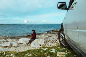 man sitting near car at seaside. road trip concept