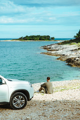 man standing near car at seaside. road trip concept
