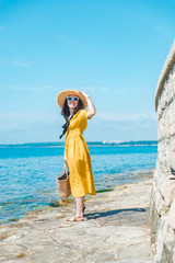 woman in yellow sundress at sea beach in straw hat