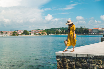 woman standing on the stone edge pier looking at sea. yellow sundress