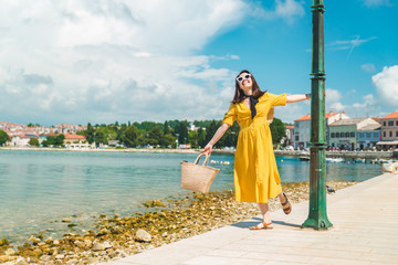 woman walking by sea quay in summer day in yellow sundress