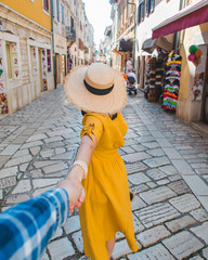 follow me concept. woman in yellow sundress in straw hat walking forward by small resort city street holding man hand