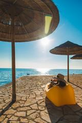 woman in yellow sundress laying at yellow sofa at sea beach