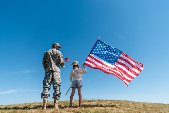 soldier in military uniform standing near kid with american flag against blue sky