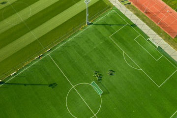Aerial view from below of a large green football field with white lined lines and players playing a match. Playing football at the stadium. Professional soccer players are located on the playing field