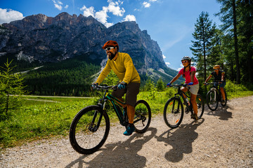 Cycling family riding on bikes in Dolomites mountains landscape. Couple cycling MTB enduro trail track. Outdoor sport activity.