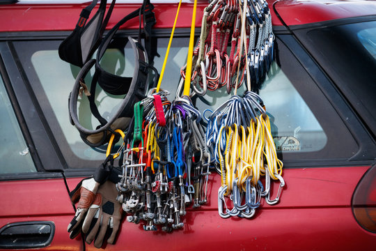 Climbing gear: a harness, cams, slings, carabiners, quickdraws, belay gloves, sit on the back of a Subaru Outback.
