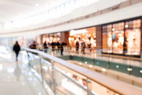 Blurred big sales on Black Friday. A long light floor in the mall with shops for buyers. Sale of clothing in a modern shopping center. The main background for the design. Shopping. Copyspace