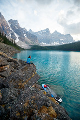 A woman takes a break from stand up paddle boarding to take in the views at Moraine Lake in Banff National Park in Canada at dusk in the summer.