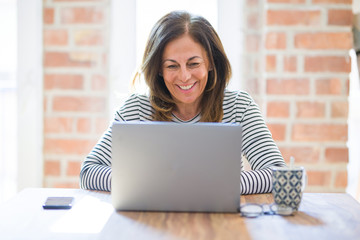 Wall Mural - Middle age senior woman sitting at the table at home working using computer laptop with a happy face standing and smiling with a confident smile showing teeth