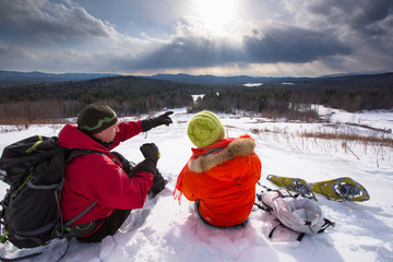 A man and woman take a hot tea break while snowshoeing in the newly-aquired 1,300 acre parcel of land at the south end of the Green Hills Preserve. The addition expanded the overall uninterrupted acreage of the preserve to 5,500 acres and as an important watershed and drainage basin for the Saco River is an important habitat for deer, black bear, moose, bobcat, fisher, brook trout, mink, beavers and  more. Portions of the acreage are undergoing revegetation and restoration of native plant species.