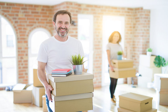 Middle age senior couple moving to a new house, man smiling happy in love with new apartment and holding cardboard boxes