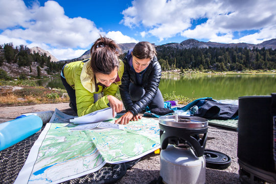 Two women look at a large map next to Skull Lake in the southern Wind River Range.