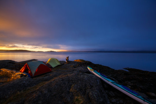 A colorful sunrise at a picturesque peninsula campsite in the south cove of Jones Island during a 3-day sea kayaking trip in the San Juan Isands of northwest Washington State. The island is a 188 acre State Park that is only accessible by boat and has 24 campsites.