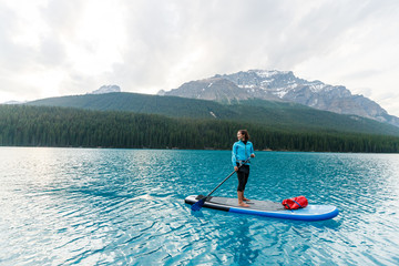 A woman stand up paddle boards at Moraine Lake in Banff National Park in Canada at dusk in the summer.