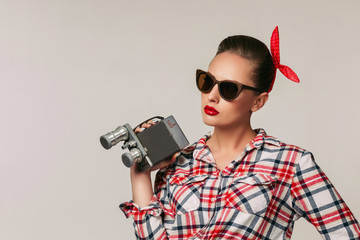 pin-up girl in plaid shirt and sunglasses holding old vintage camera.