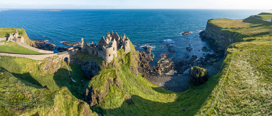 Staande foto Kust Ruins of medieval Dunluce Castle on a steep cliff. Northern coast of County Antrim, Northern Ireland, UK. Aerial wide panorama in sunrise light