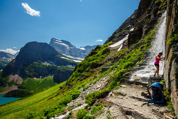 A woman cools off in a waterfall that cascades over the trail up to the Grinell Glacier in the Many Glacier area of Glacier National Park. Grinell Lake is in the background.