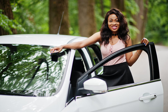 African american woman posed against white car in forest road.