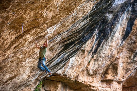 A man on Victimes del passat 8c (5.14b) at the Roca de Finestra wall near Maragalef, Spain.