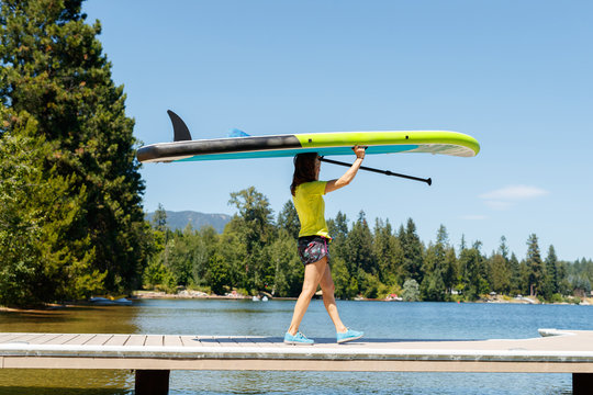A woman walks down a dock holding  a stand up paddle board in preparation for some SUP at Lake Pend Oreille in northern Idaho.