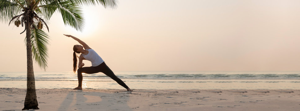 Yoga woman doing yoga exercise on the beach.